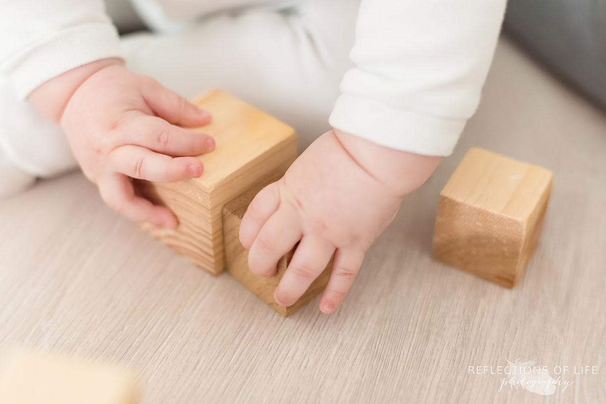 baby's hands with blocks on studio floor.jpg