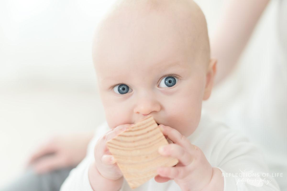baby boy looking at camera with block.jpg