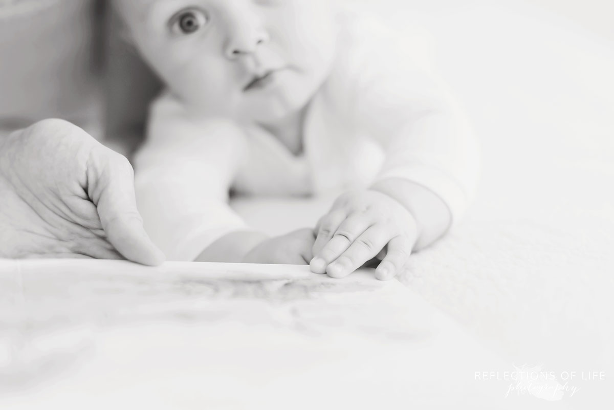 baby boy reading book black and white.jpg