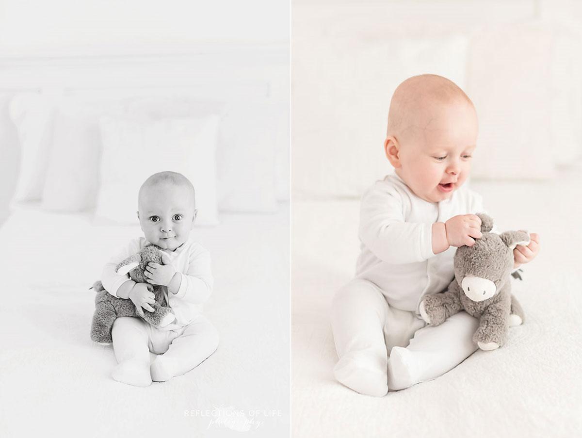 baby boy sitting on bed with stuffed animal.jpg