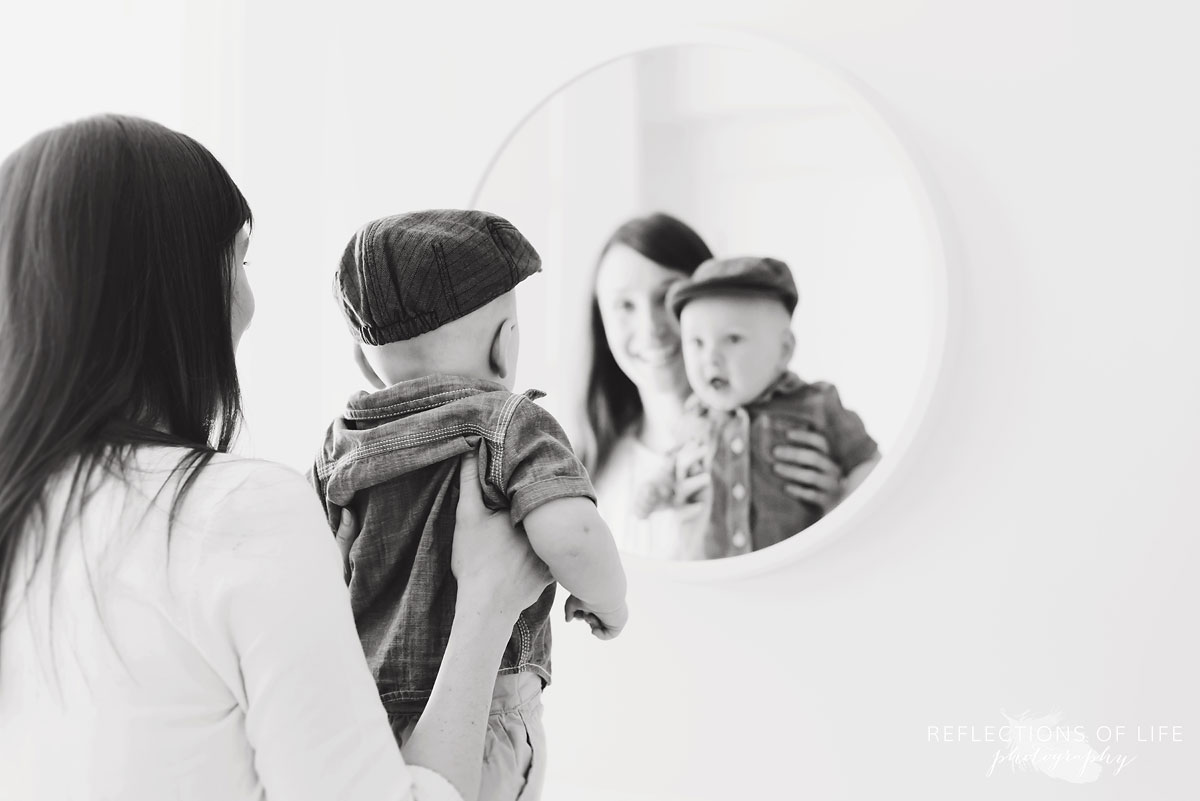 mom and baby looking in mirror in studio black and white.jpg