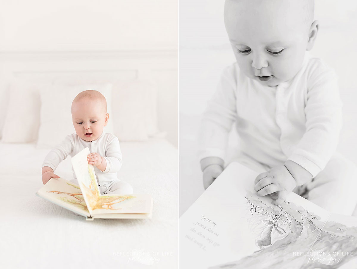 baby boy reading book while sitting on white bed in studio.jpg