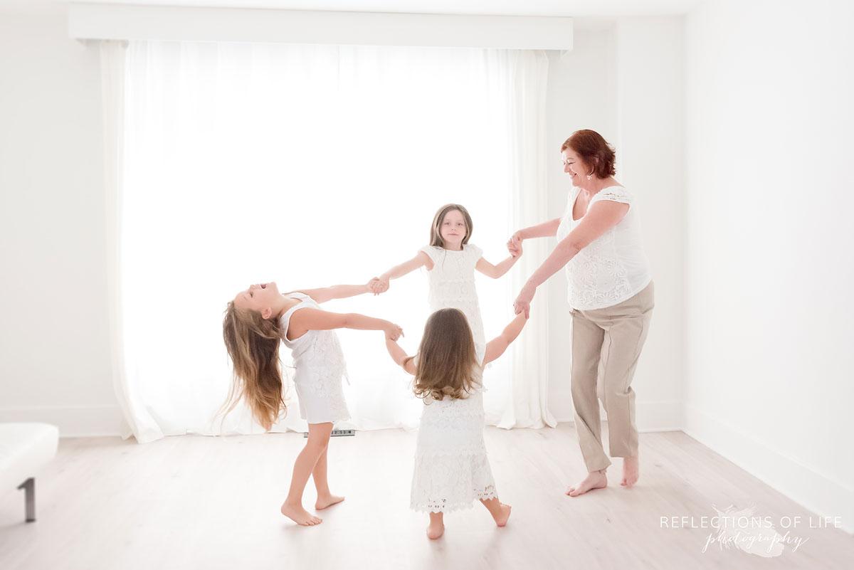Grandma and granddaughters dancing by the window in natural light studio