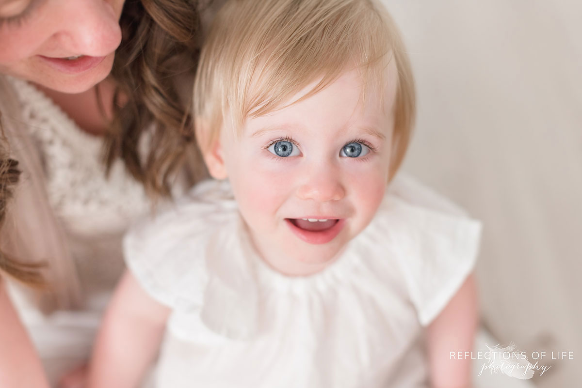 little girl looking up at the camera with wide open blue eyes