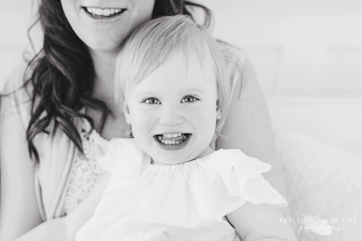 little girl smiling at the camera in black and white