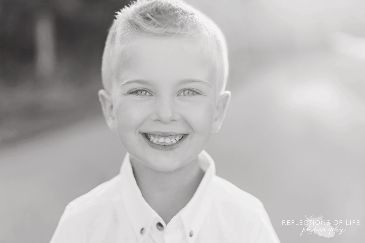 Little boy smiling at the camera in black and white