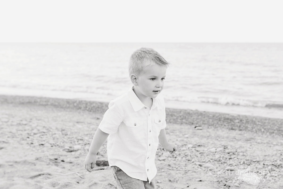 Little boy walking down the sandy beach