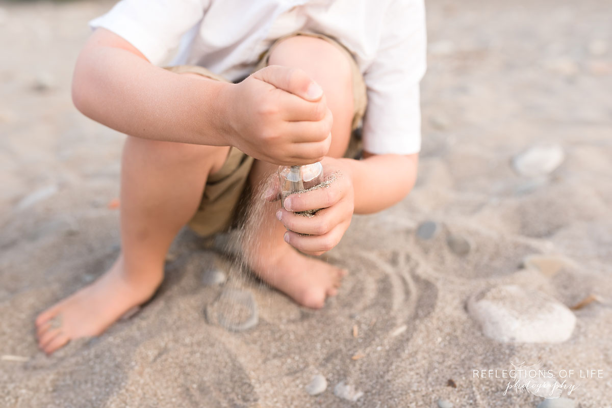 Little boy filling glass bottle with sand at Casablanca Beach