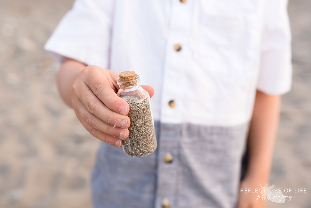 Little boy showing off is sand jar at the beach