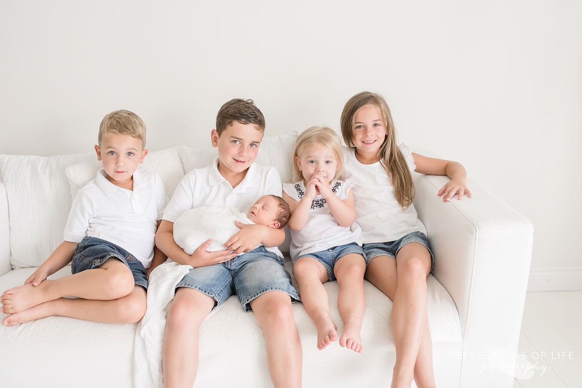 Family of 5 siblings hold their new baby brother on the couch