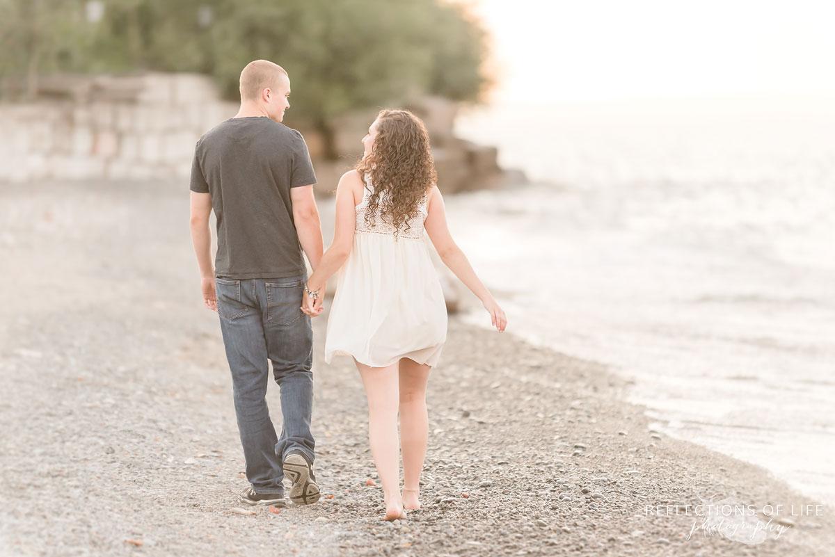 Girlfriend and boyfriend walking along the beach holding hands