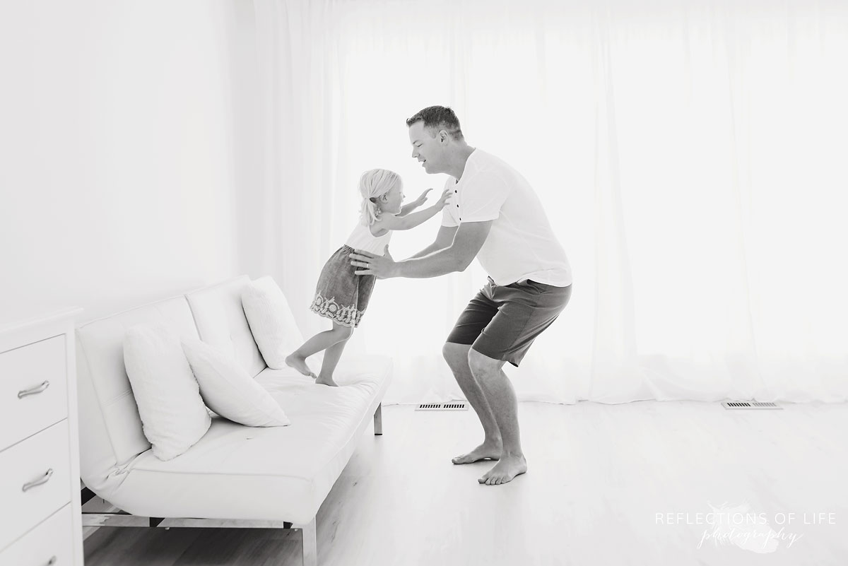 Girl jumping into daddys arms off white couch