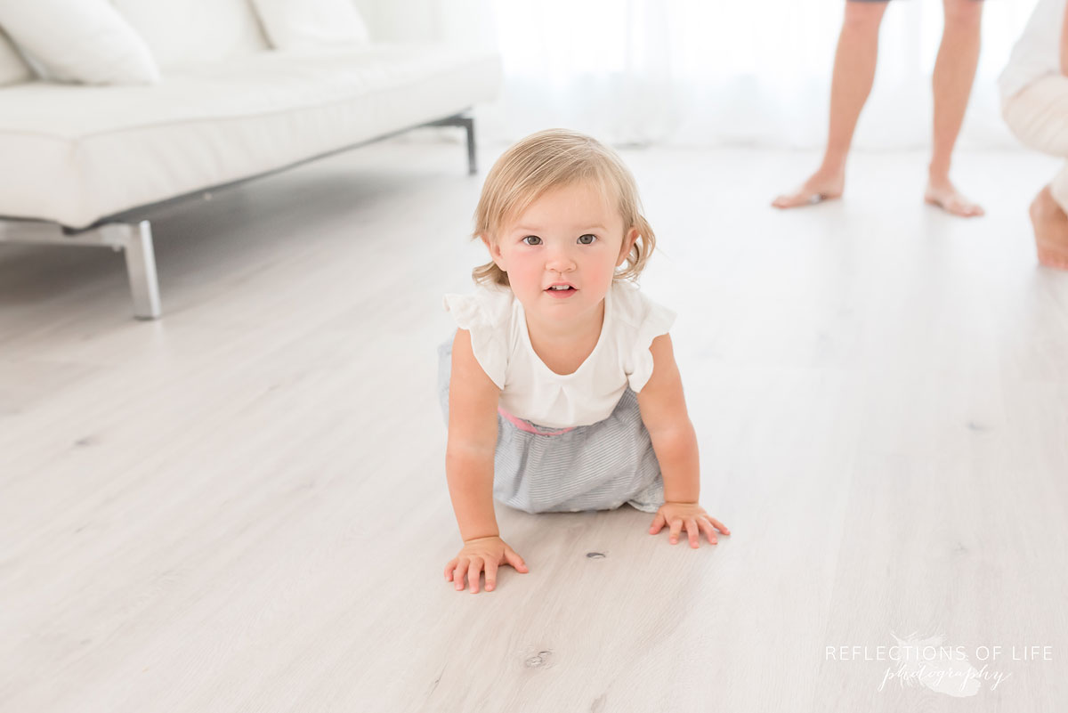 little girl crawling on floor in white studio