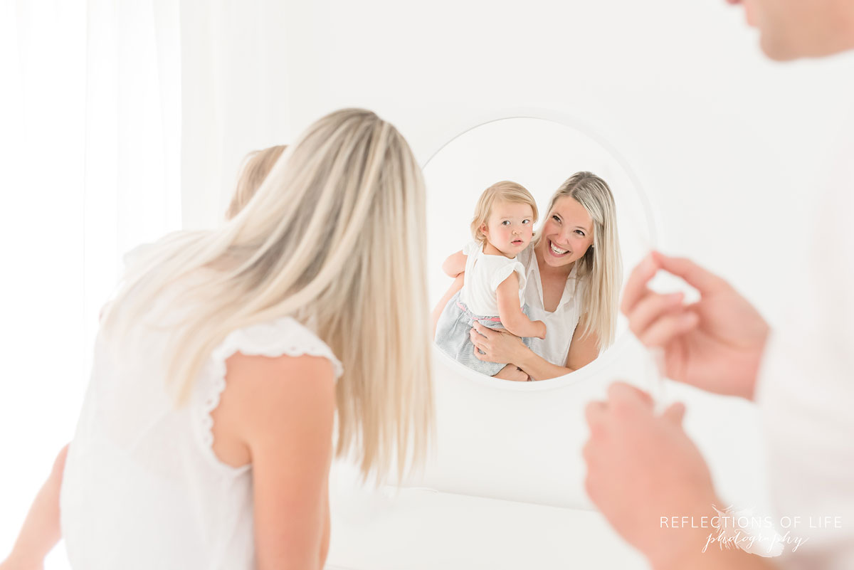 mother and daughter looking into mirror in white studio