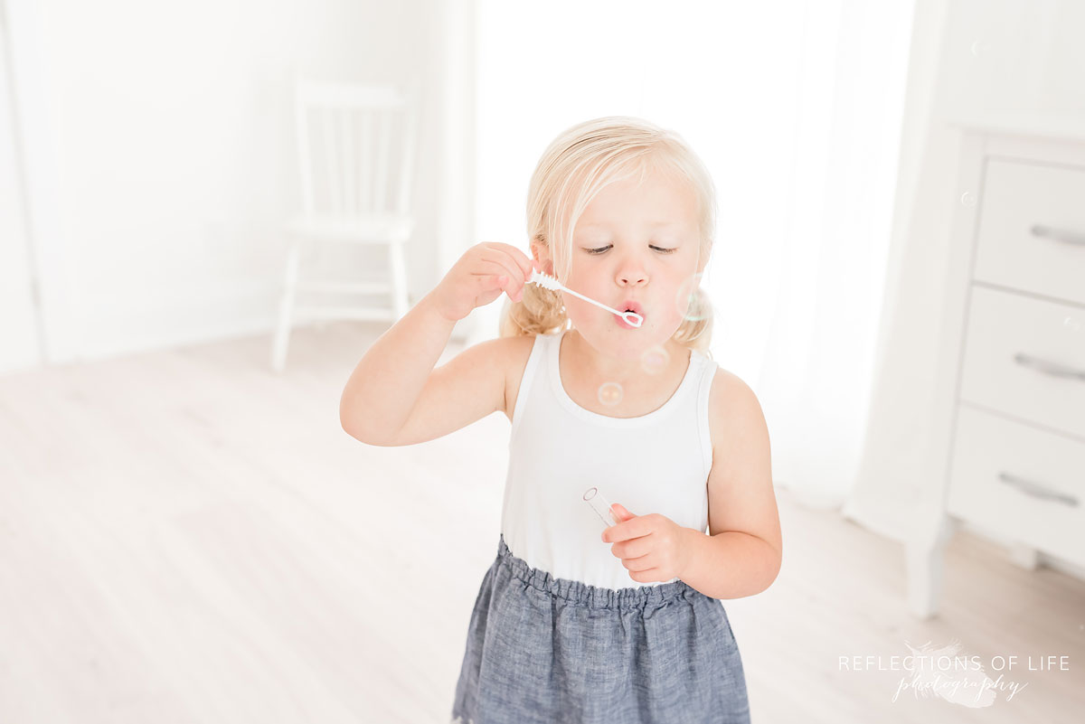 little girl blowing bubbles in white studio
