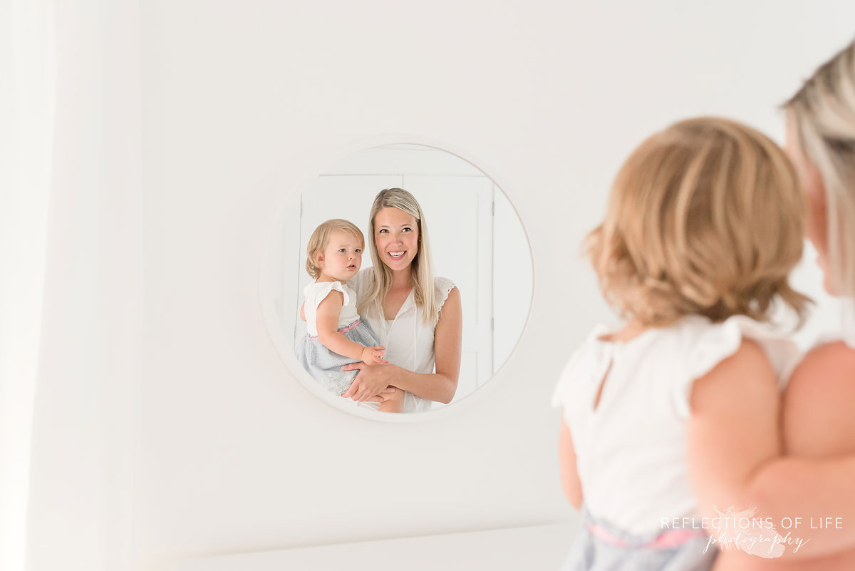 mom and daughter looking into mirror