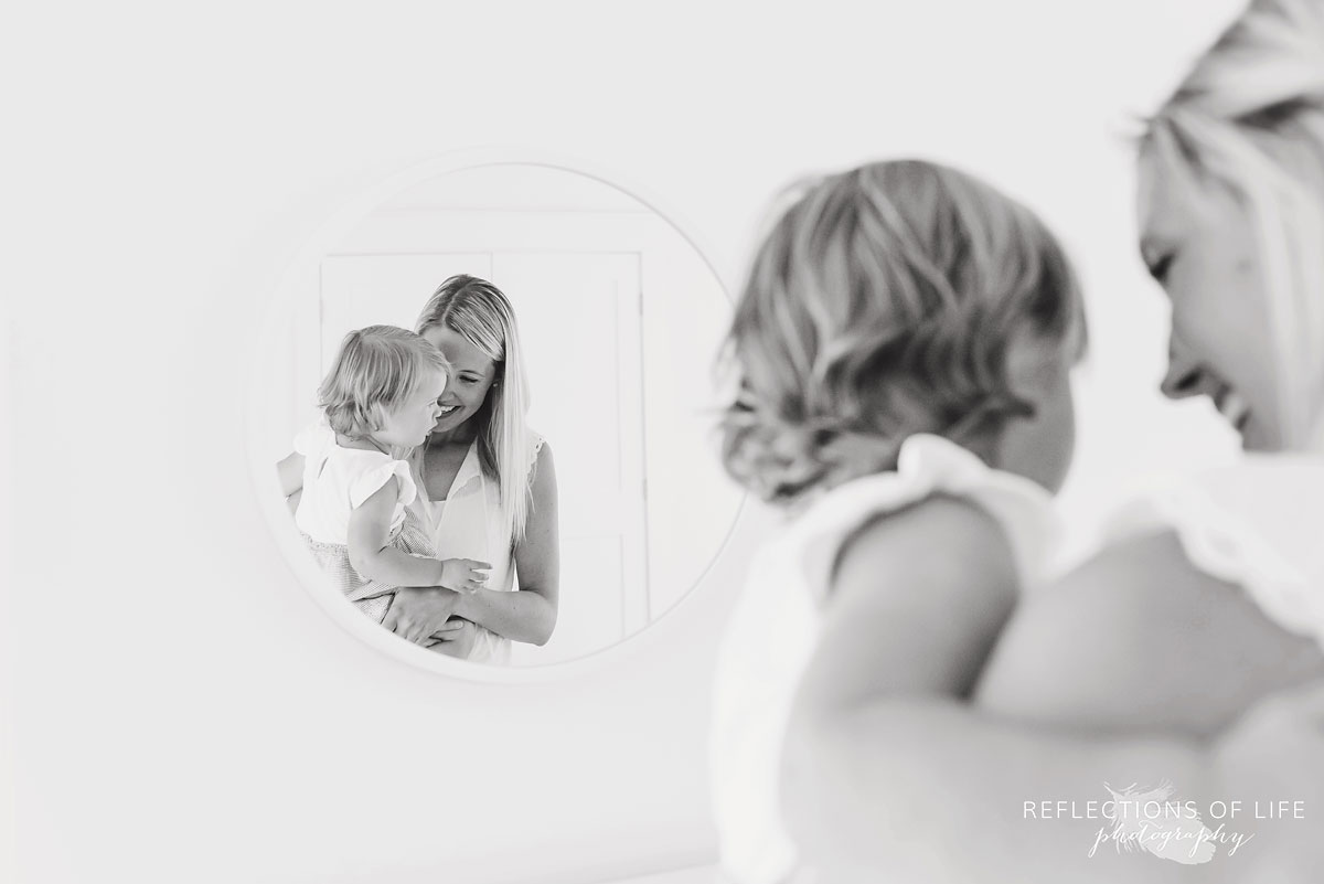 black and white of mom and daughter looking into mirror