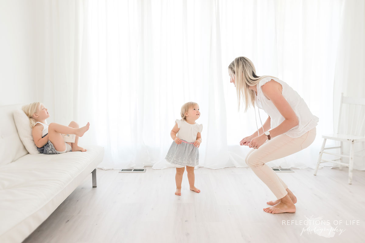 mom and daughters dancing in white studio