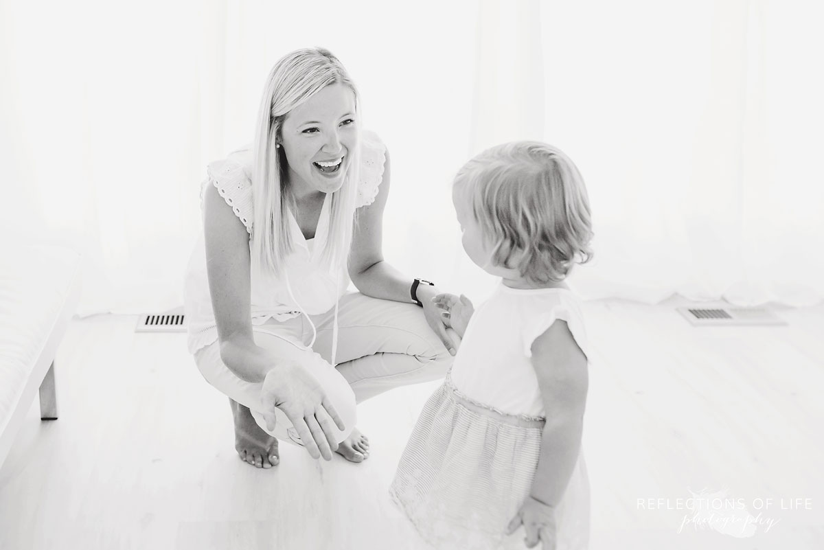 black and white of mom opening her arms to daughter