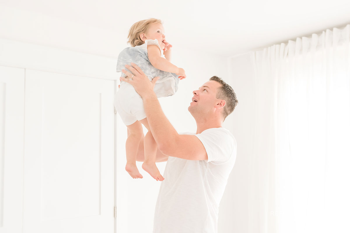 dad holding baby up high