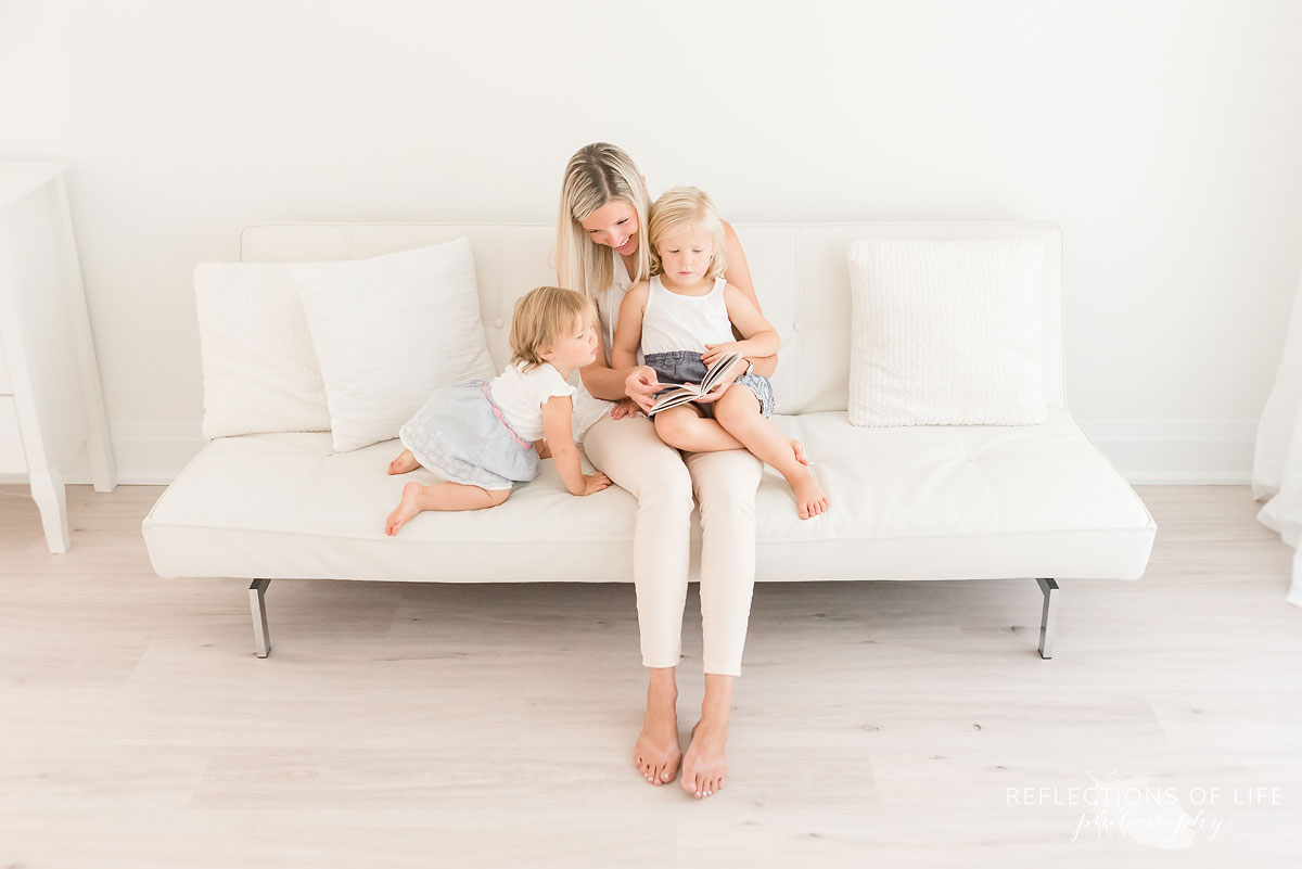 mom and daughters reading a book on white couch