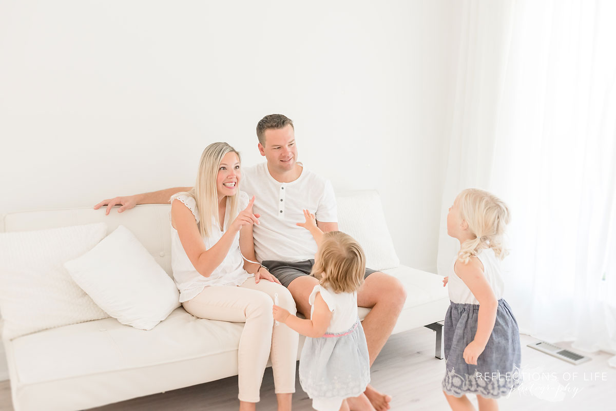 family playing on white couch