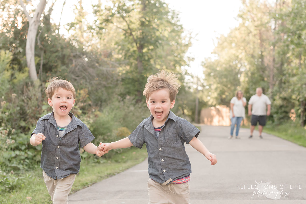 Two boys running, holding hands as parents watch