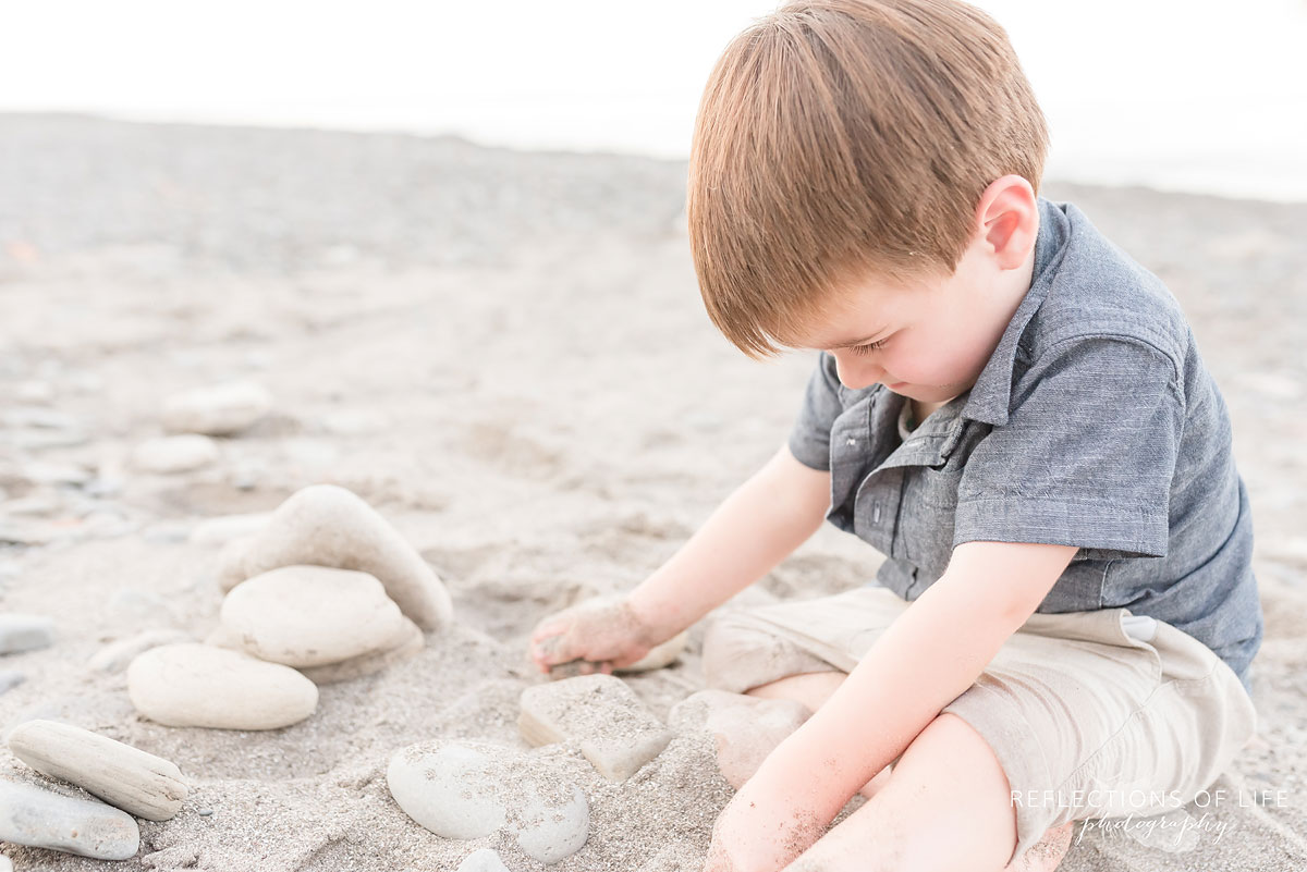 boy sitting on the sand playing with rocks