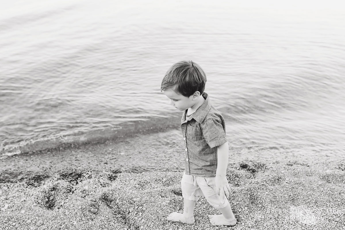 young boy walking down the beach black and white