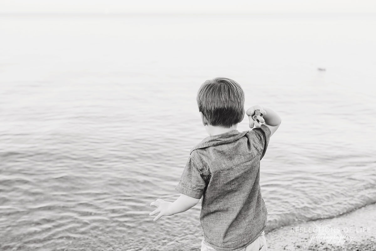 boy throwing a rock into the water black and white