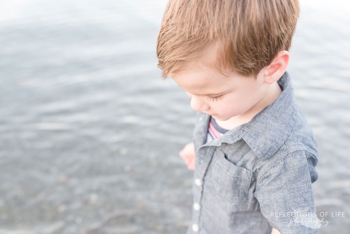 close up shot of a young boy looking down by the water
