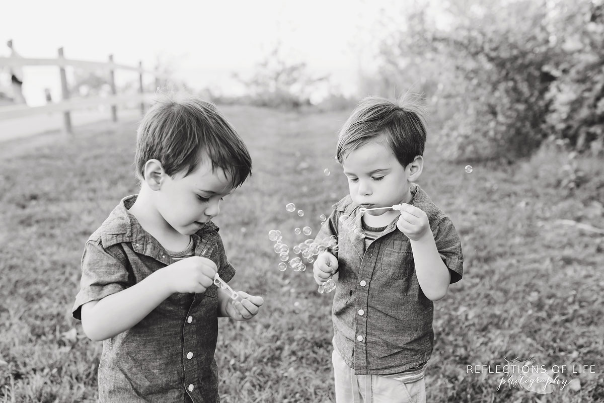 two young boys blowing bubbles black and white by Karen Byker