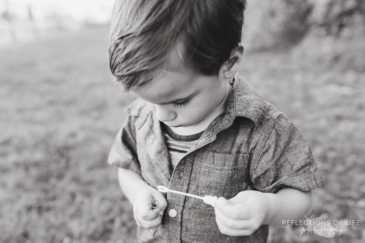Young boy playing with bubbles black and white