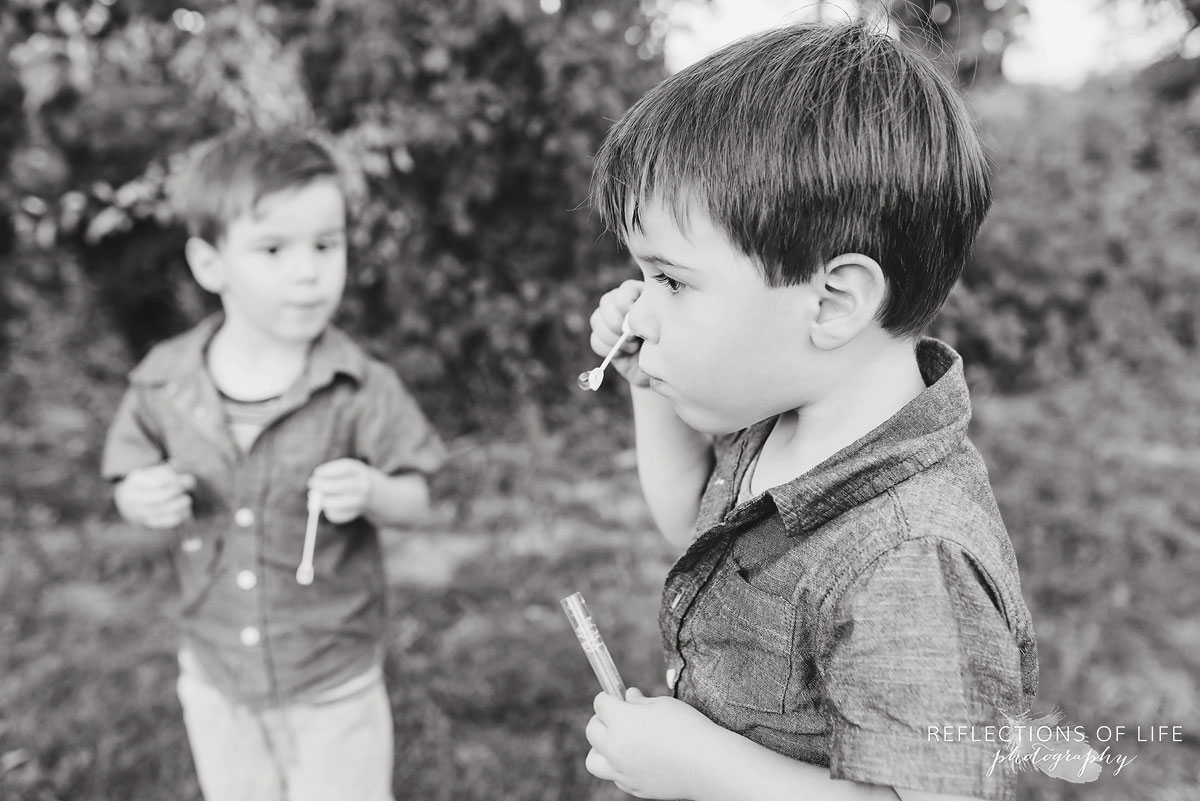 two boys blowing and playing with bubbles black and white