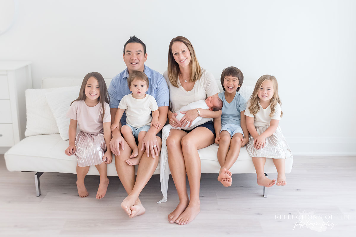 family of seven sitting on a couch in a studio smiling