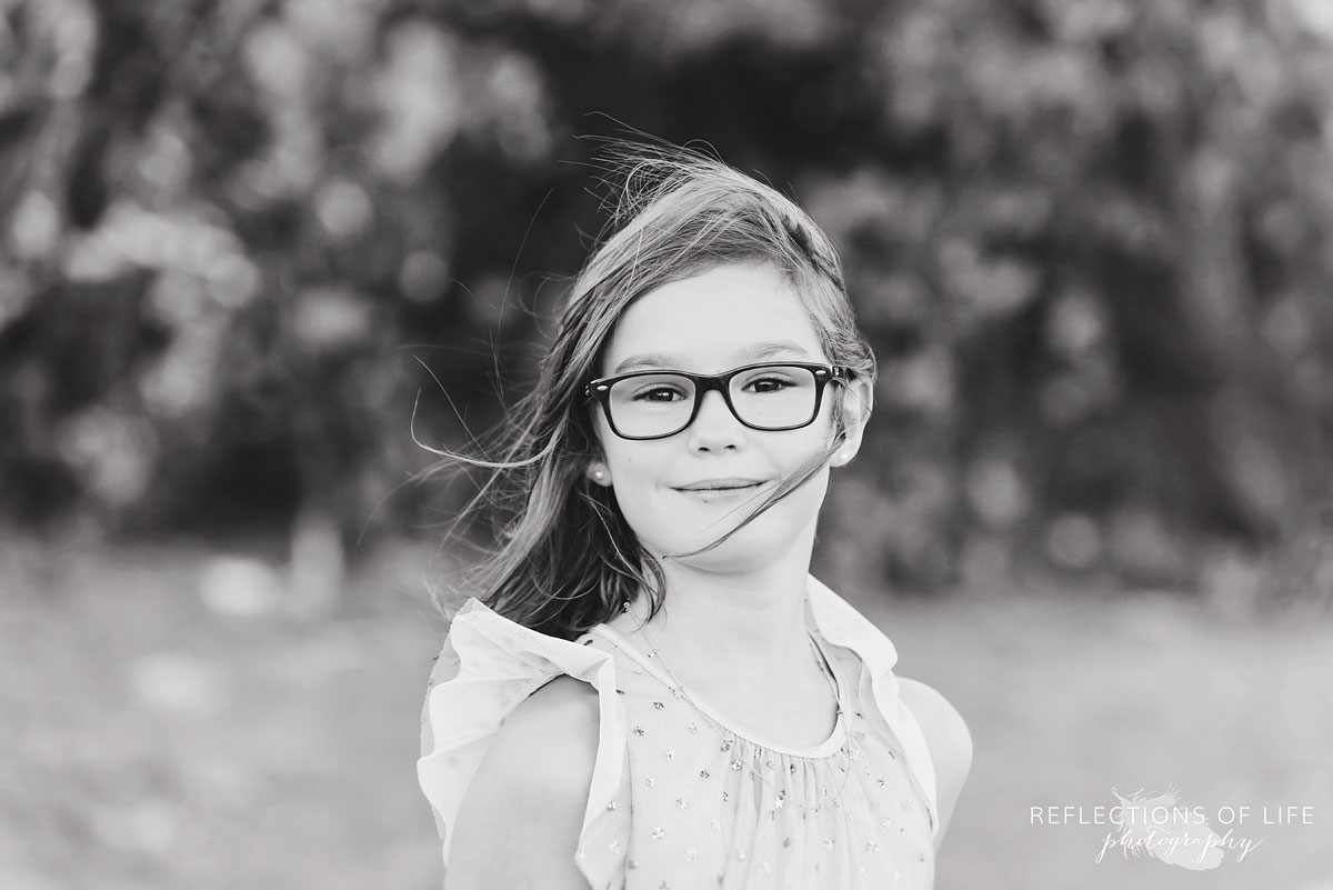black and white of young girl with glasses smiling at camera