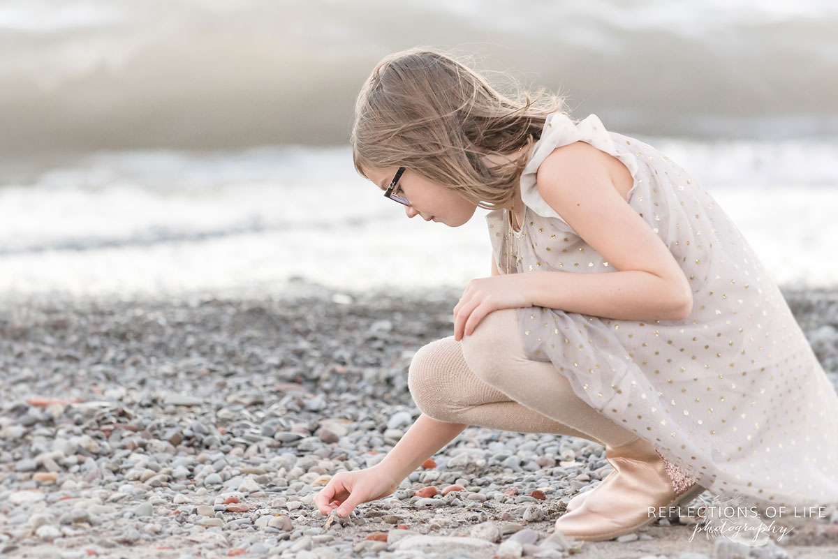 little girl looking at rocks on beach