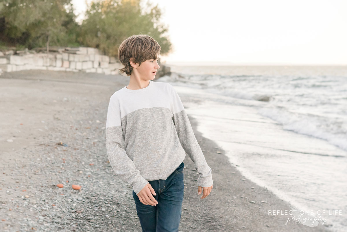 boy looking at beach after throwing rocks into water