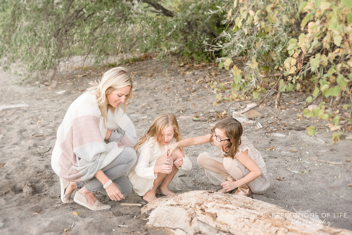 mother and daughters looking at rocks on beach