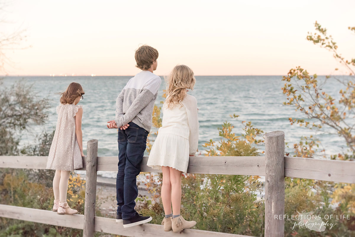 three sibling looking out at beach by wooden fence