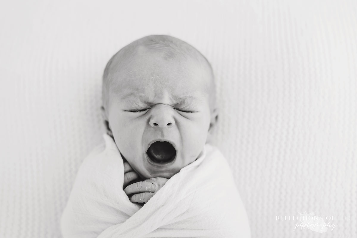 baby yawning in black and white