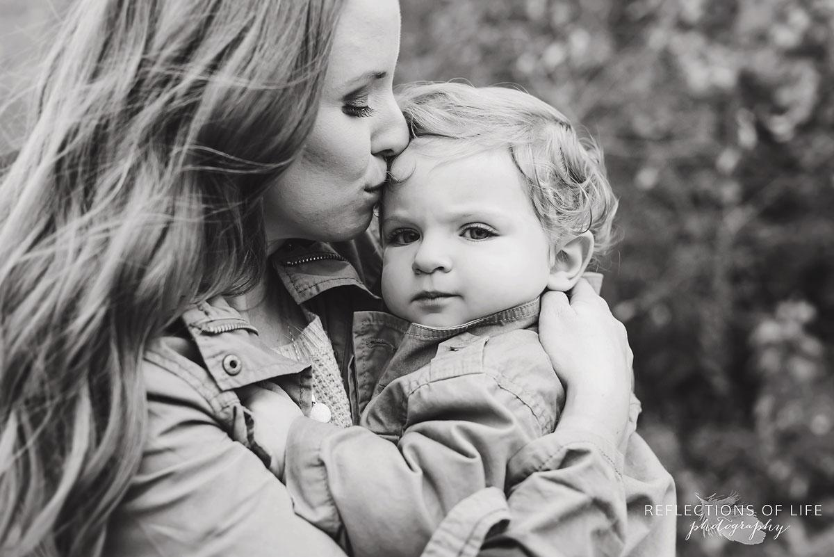 mothing kissing her child black and white