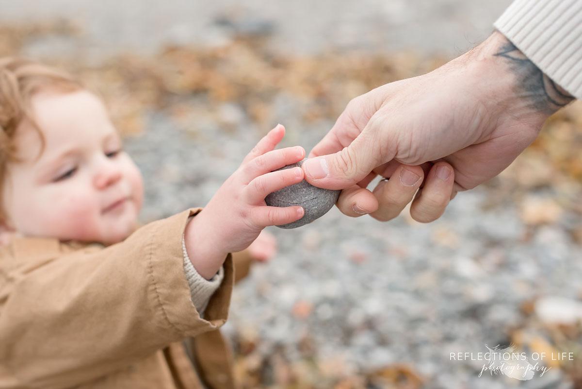 dad handing child a rock
