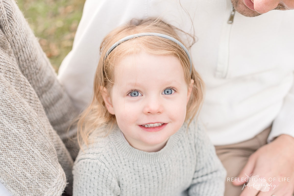 little girl with blue eyes smiling at camera