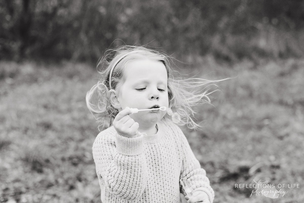 little girl blowing bubbles outdoors