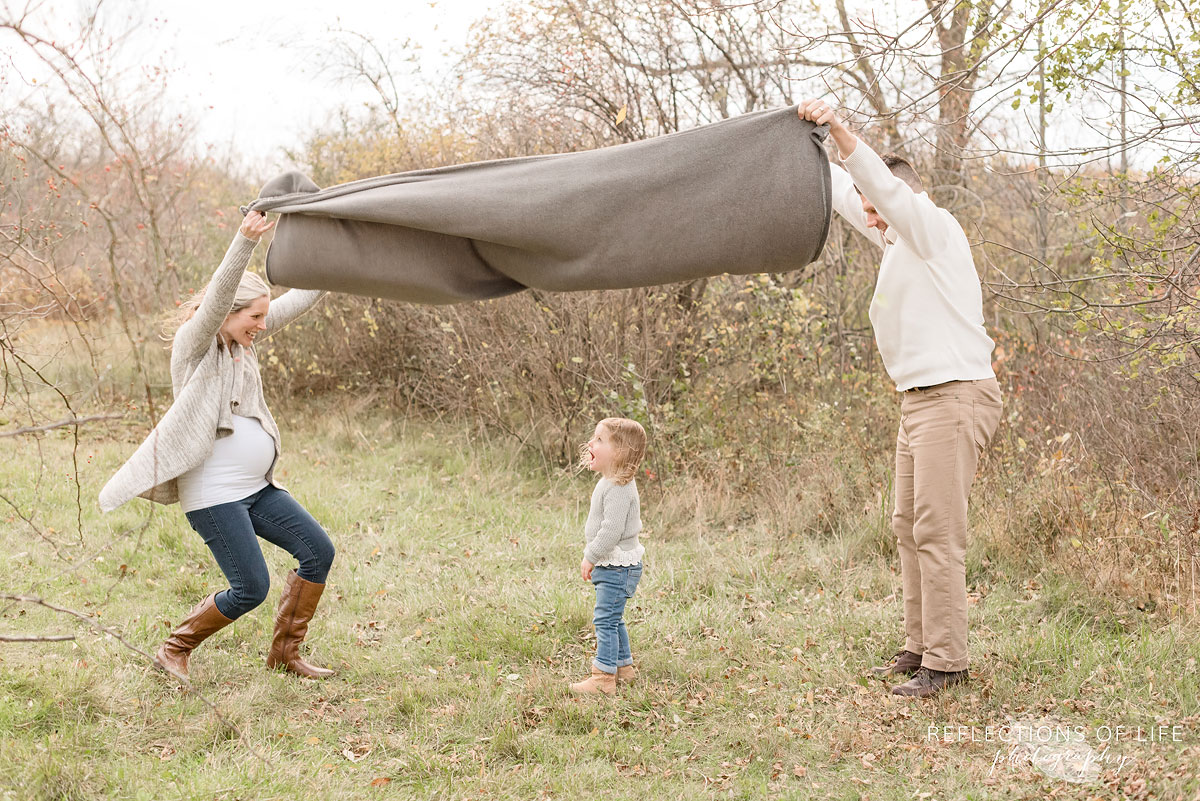 parents holding blanket over little daughter