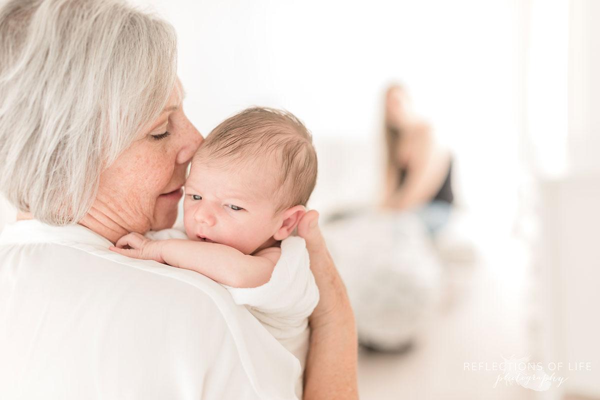 grandma holding newborn in white studio