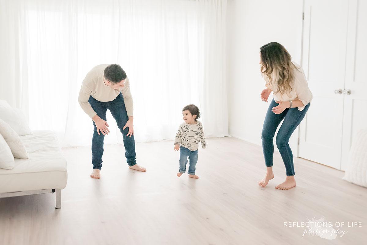 family dancing around in white studio