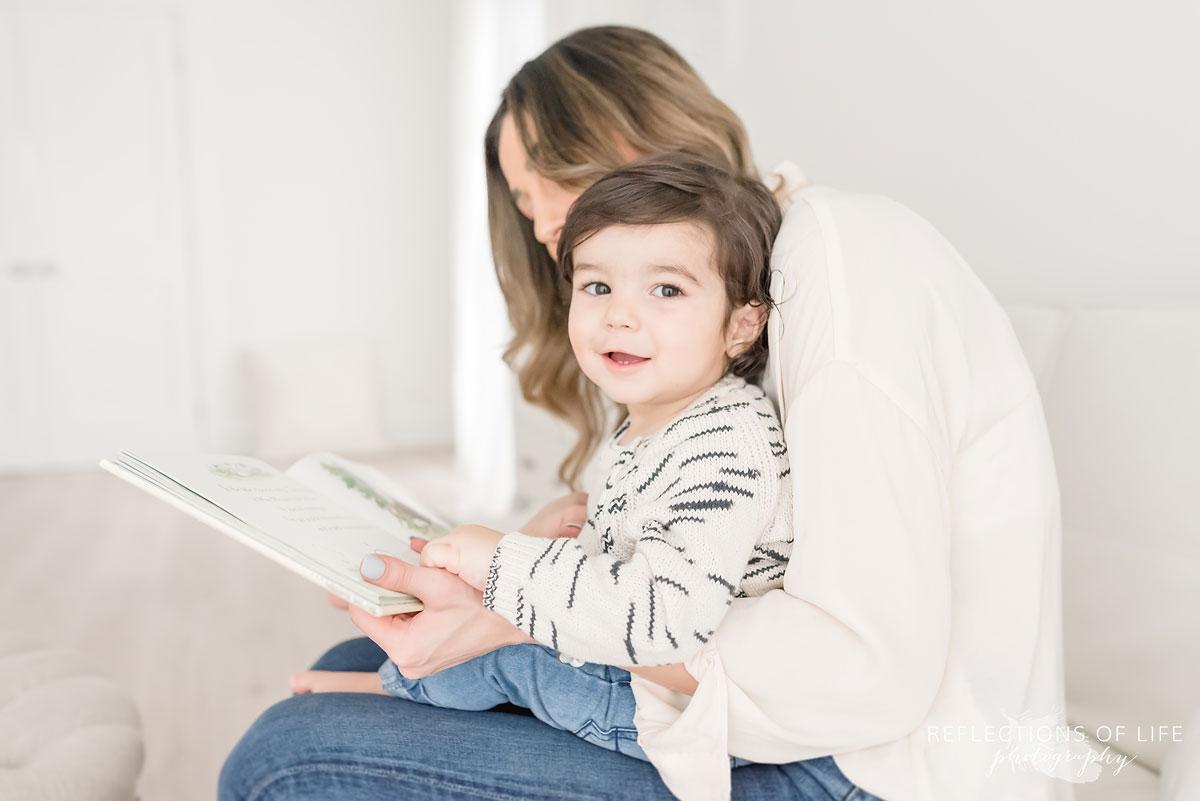 son smiling at camera while reading