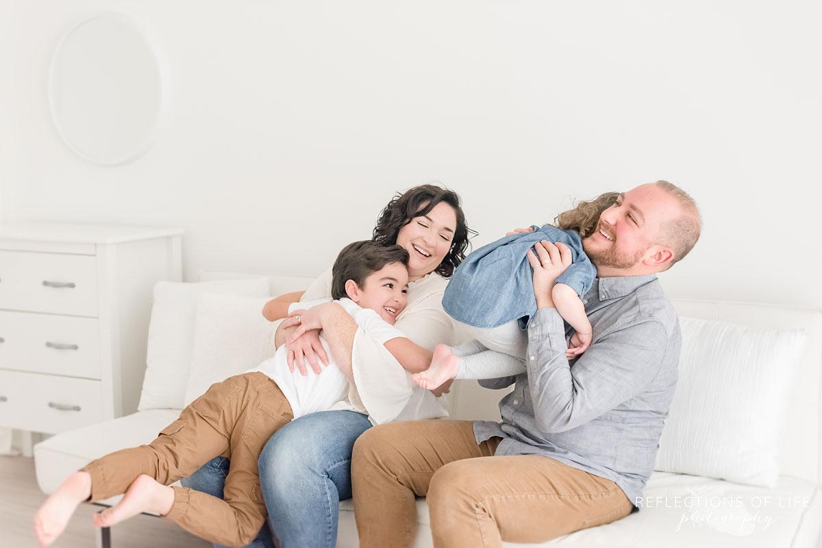 family hugging in white studio